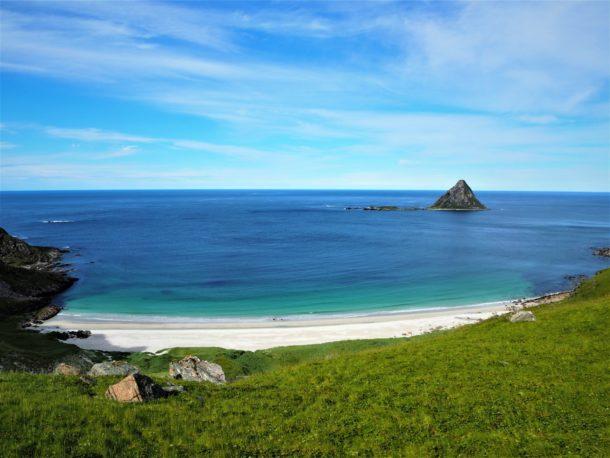 Plage déserte avec vue sur l'océan et une petite île sombre, Lofoten